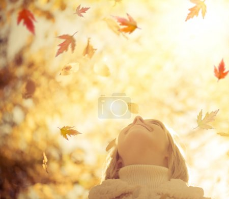 Photo for Happy child with maple leaves in autumn park against yellow blurred leaves background. Freedom concept - Royalty Free Image