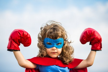 Photo for Superhero kid wearing boxing gloves against blue sky background. Girl power and feminism concept - Royalty Free Image