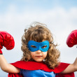 Superhero kid wearing boxing gloves against blue s...