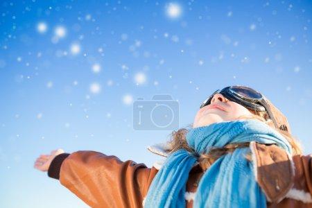 Photo pour Enfant heureux jouant avec jouet avion sur fond bleu ciel d'hiver - image libre de droit