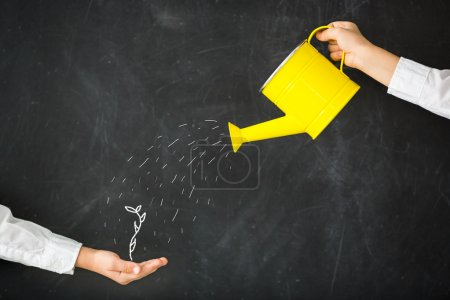 Photo for Watering can in hand against blackboard - Royalty Free Image