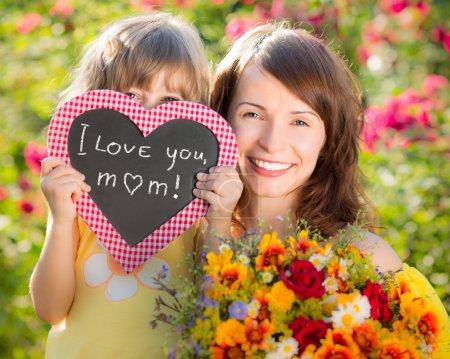 Photo pour Femme et enfant avec bouquet de fleurs sur fond vert. concept de ressort de vacances familiales. fête des mères - image libre de droit