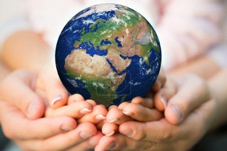 Photo pour Famille tenant la Terre entre les mains. Éléments de cette image fournis par la NASA - image libre de droit