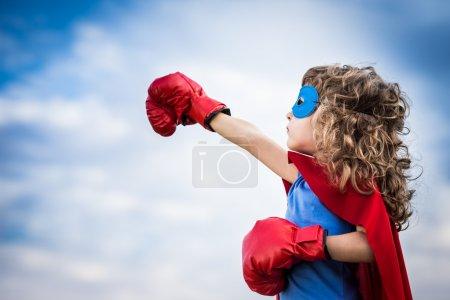 Foto de Niño superhéroe contra el fondo del cielo de verano. El poder femenino y el concepto feminista - Imagen libre de derechos