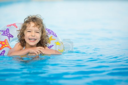 Photo for Happy child playing in swimming pool. Summer vacations concept - Royalty Free Image