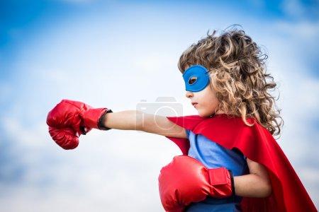 Foto de Superhéroe niño contra dramático cielo azul fondo - Imagen libre de derechos