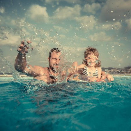 Photo for Happy family playing in swimming pool. Summer vacations concept - Royalty Free Image