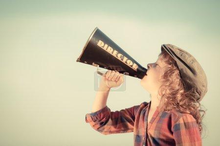 Photo pour Un gamin criant à travers un mégaphone vintage. Concept de communication. Fond bleu ciel comme espace de copie pour votre texte - image libre de droit