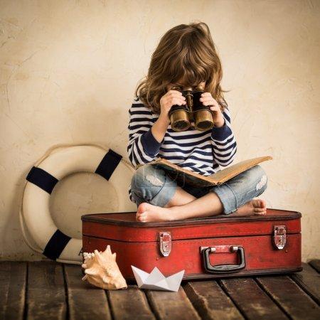 Photo pour Enfant heureux jouant avec un voilier jouet à l'intérieur. Concept de voyage et d'aventure - image libre de droit