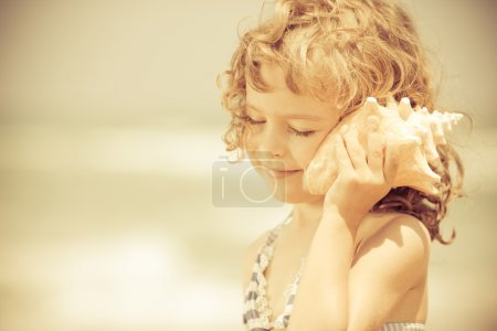 Photo for Happy child listen to seashell at the beach. Summer vacations concept - Royalty Free Image