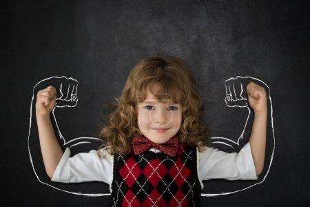 Photo pour Un gosse fort en classe. Joyeux enfant contre tableau noir. Concept d'éducation - image libre de droit