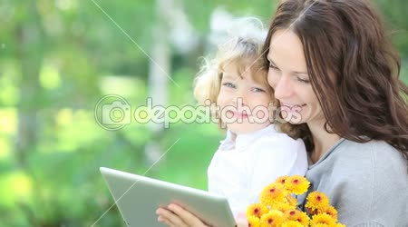 Happy family using tablet PC outdoors in spring park