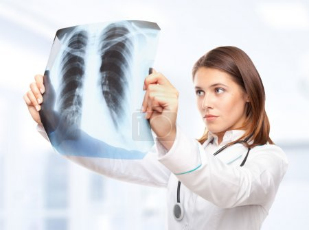 Photo pour Jeune femme médecin regardant l'image radiographique des poumons à l'hôpital - image libre de droit