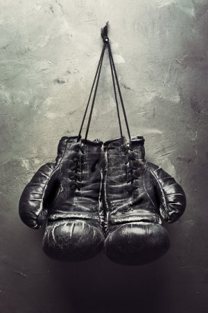 old boxing gloves hang on nail
