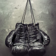Old boxing gloves hang on nail on texturе wall. R...