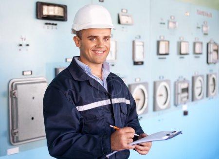 Photo pour Portrait de jeune ingénieur souriant, prendre des notes à la salle de contrôle - image libre de droit