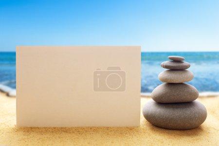 Photo pour Pyramide des pierres avec papier blanc sur la plage de sable à fond océanique - image libre de droit