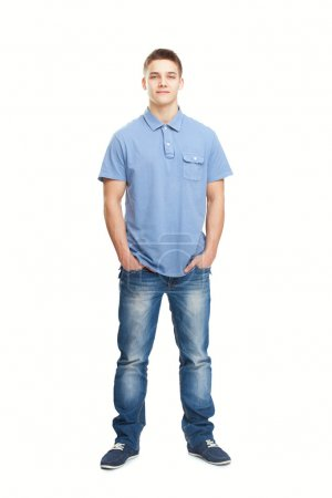 smiling young man standing with hands in pockets