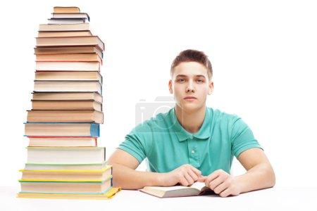 Photo pour Étudiant étudiant à une table avec des livres élevés empilent isolé sur fond blanc - image libre de droit
