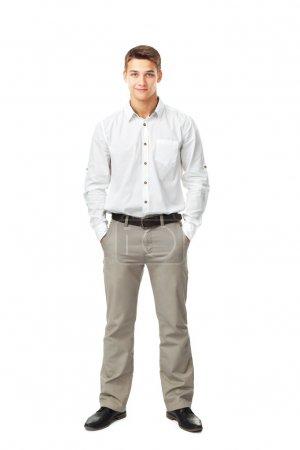 Photo pour Portrait complet de jeune homme portant chemise blanche et pantalon léger avec les mains dans des poches isolées sur fond blanc - image libre de droit