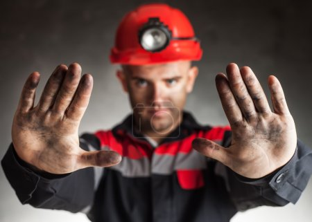 Coal miner with dirty hands making stop gesture wa...