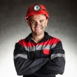 Portrait of happy smiling coal miner with his arms...