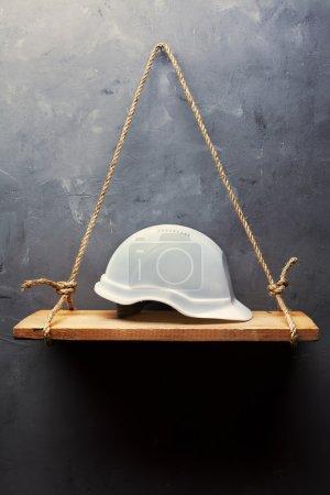 White helmet on the old wood shelf