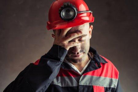 Photo pour Portrait d'un mineur de charbon fatigué tenant la main sa tête sur un fond sombre - image libre de droit