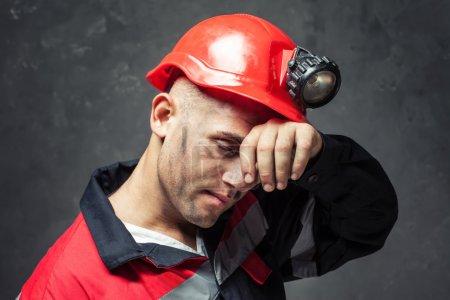 Photo pour Portrait d'un mineur de charbon fatigué essuyant le front de sa main sur un fond sombre - image libre de droit