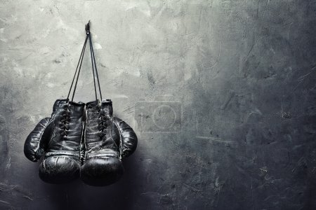 Photo for Old boxing gloves hang on nail on texture wall with copy space for text. Retirement concept - Royalty Free Image