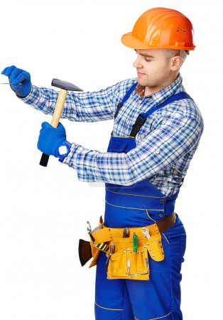 Working man with hammer driving a nail in wall