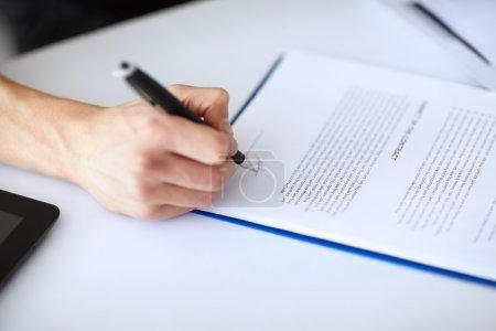 Photo pour Jeune entrepreneur, signature de document à table en gros plan Bureau blanc - image libre de droit