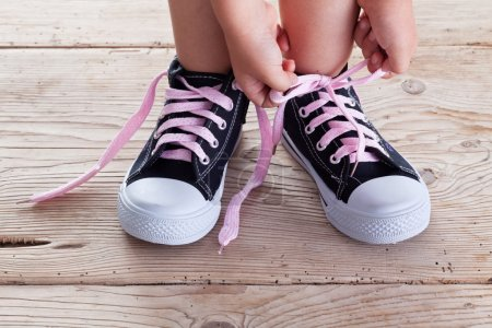Photo for Child hands tie up shoe laces on old wooden floor background - Royalty Free Image