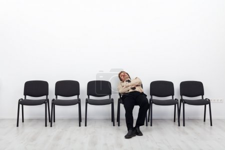 Photo for Tired businessman waiting - sitting on a chairs row - Royalty Free Image