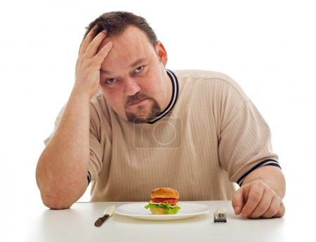 Photo pour Homme désespéré de ne pas avoir assez à manger - focus sur les aliments et la plaque - image libre de droit