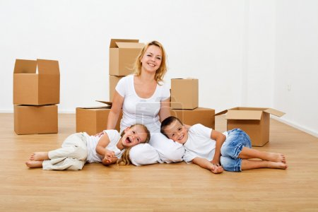 Photo for Family moving into a new house - having fun among scattered cardboard boxes - Royalty Free Image