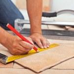 Laying ceramic floor tiles - man hands marking til...