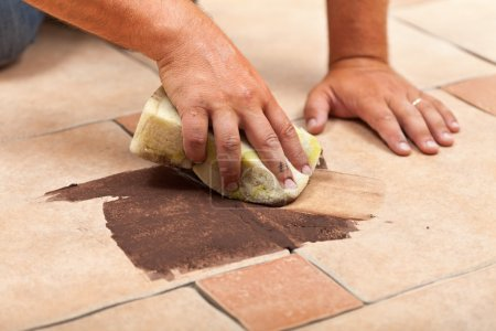 Photo for Laying ceramic floor tiles - man hands testing the color of joint on a small area - Royalty Free Image