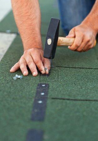Photo pour Travailleur installe des bardeaux de toiture bitume - gros plan sur les mains avec des clous et marteau - image libre de droit