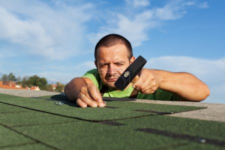 Man installing or repairing roof with bitumen shingles