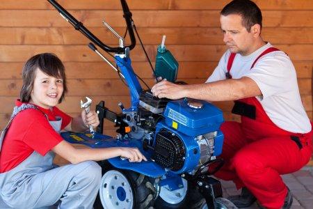 Man and boy preparing a cultivator machine for work