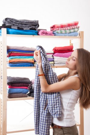 Photo for Young caucasian woman standing near the wardrobe and holding clothes - Royalty Free Image
