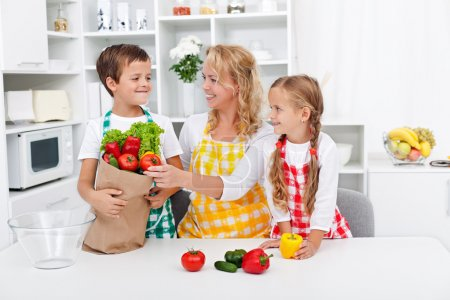 Photo for Healthy nutrition concept with in the kitchen unpacking the vegetables from grocery bag - Royalty Free Image