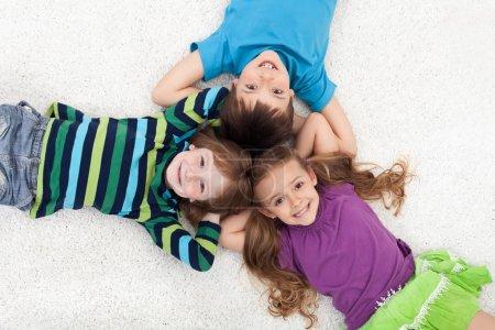 Photo pour Enfant heureux couché sur le sol tête à tête - image libre de droit