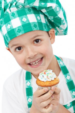 Child with chef hat holding muffin