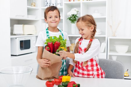 Photo for Kids unpacking the groceries in the kitchen - making fresh vegetables salad - Royalty Free Image
