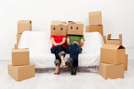 Photo for Couple in their new home with cardboard boxes, sitting on covered sofa - Royalty Free Image