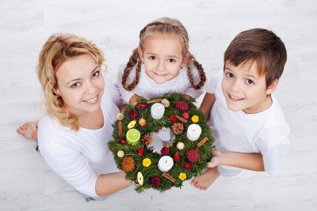 Photo pour Femme avec deux enfants tenant une couronne de l'avent - vacances en famille - image libre de droit