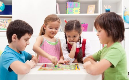 Photo for Children playing board game - sitting around a small table - Royalty Free Image