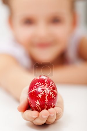 Little girl with one red easter egg